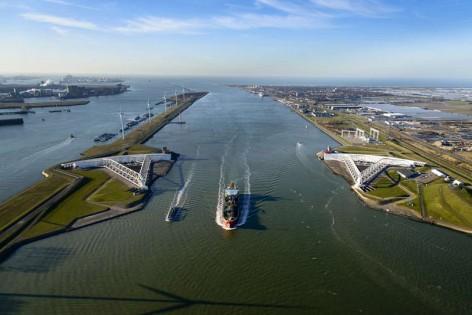 Nederland, Zuid-Holland, Rotterdam, 18-02-2015; Maeslantkering in de Nieuwe Waterweg, gezien naar de Noordzee en Tweede Maasvlakte (MV2). Links het Calandkanaal en de Maasvlakte, rechts aan de horizon Hoek van Holland. De stormvloedkering bestaat uit twee deuren die klaar liggen in een dok en welke sluiten bij een waterstand van 3 meter of meer boven NAP. De kering, laatst voltooide onderdeel van Deltawerken, beschermt Rotterdam en achterland bij extreme waterstanden. The new storm surge barrier (Maeslantkering) in the Nieuwe Waterweg (New Waterway, the entrance to the port of Rotterdam), North Sea at the horizon. In case of storm floods, the two enormous doors will close of the waterway protecting Rotterdam and its hinterland luchtfoto (toeslag op standard tarieven); aerial photo (additional fee required); copyright foto/photo Siebe Swart