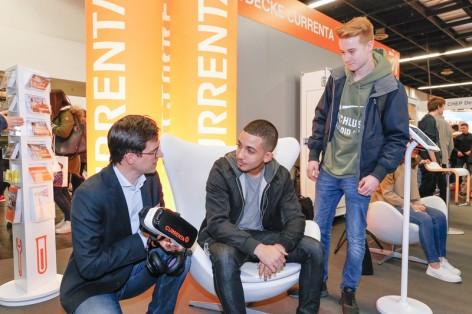 Unser Bild zeigt Jörg Michael (im Bild links), Leiter Currenta Personalgewinnung, der interessierten Schülern auf der Studien- und Ausbildungsplatzmesse Berufe live Köln den Umgang mit der neuen Virtual-Reality-Brille erklärt.