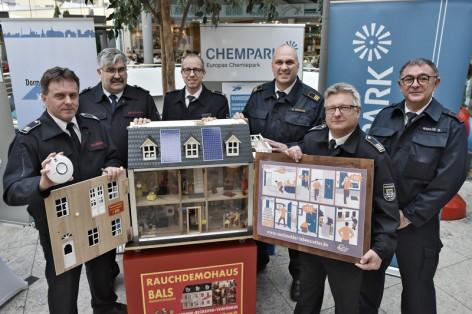 """Bernd Eckardt (2.v.r.), Leiter der Feuerwehr Dormagen, und seine Kollegen Wolfgang Feige (l.) und Gerd Gleich (2.v.l.) sowie Oliver Krause (3.v.r.), Leiter der Werkfeuerwehr im Chempark Dormagen, und seine Kollegen Dieter Jülich (3.v.l.) und Robert Werlik (r.) vor dem """"Rauchdemohaus""""."""